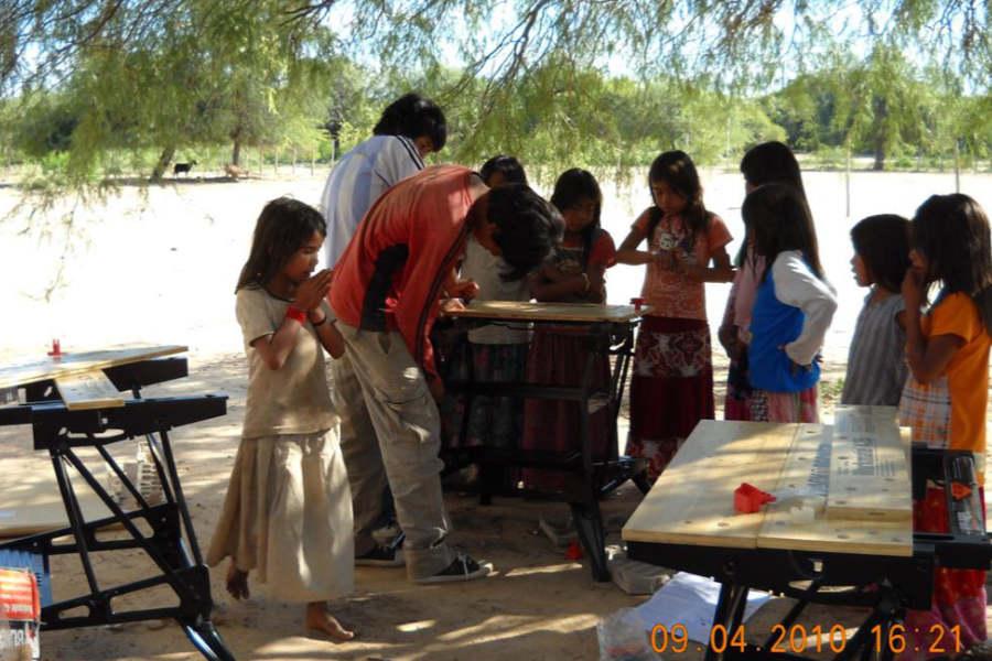 Die Werkbänke werden nach Anleitung montiert. Die Kinder des Dorfes sind herbei gerannt, um zuzuschauen.