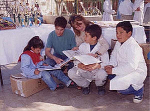 Alejandra von Edumanía überreicht Bücher für die Schulbibliothek.