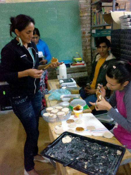 """Schüler*innen beim Herstellen von Süßspeisen aus regionalen Produkten: z.B. """"mamón"""", eine Süßspeise aus einer Papayaart oder die Doca-Süßspeise aus der Frucht einer wilden Kletterpflanze. Die Schüler*innen lernen, wie angebaute oder wild wachsende Pflanzen der Region zur Lebensmittelherstellung genutzt werden können.."""